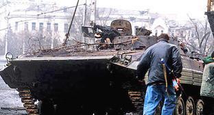 Чеченский боевик возле сгоревшей боевой машины пехоты. Грозный, январь 1995 г. Фото: Михаил Евстафьев https://ru.wikipedia.org/