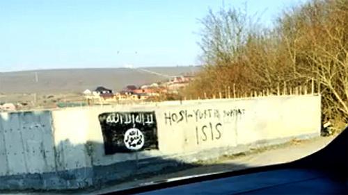 Изображение флага, используемого боевиками «Исламского государства» (признанного 29 декабря 2014 г. Верховным судом России террористической организацией), на стене в селении Хосе-Юрте. Фото: Стоп-кадр видео ИГИШ в Хоси -Юрте / IG in Chechnya, http://www.youtube.com/watch?v=n2sVCqLfPp0