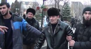 Отец Магомеда Аушева (второй справа) возле Республиканской клинической больнице в Нальчике. Кадр из видео Официальный канал МЕХК-КХЕЛ http://www.youtube.com/watch?v=jpYuIpOYB1c