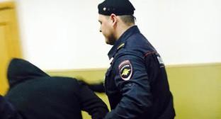"""Сотрудник полиции конвоирует подозреваемого в зал суда. Фото Юлии Буславской для """"Кавказского узла"""""""