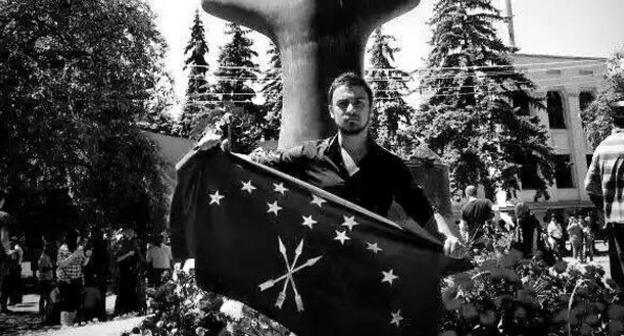 Нартан Кылыч держит черкесский флаг перед памятником жертвам Кавказской войны в Нальчике. Фото:  Аслан Щакуэ, Фатима Тлисова и Ольга Эфендиева-Бегрет https://www.facebook.com/photo.php?fbid=10153411014089002&set=a.10150641558564002.436428.531449001&type=1&fref=nf&pnref=story