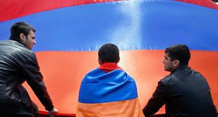 Молодые люди держат полотно с цветами армянского флага. Фото: http://www.szona.org/ne-provedete-i-obshhestvennyj-front-spaseniya-gotovy-vystupit-edinym-frontom/