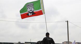 """Сотрудник чеченского СОБРа с флагом республики, на который наложен портрет Ахмата Кадырова. 9 мая 2015 года, Грозный. Фото Магомеда Магомедова для """"Кавказского узла"""""""